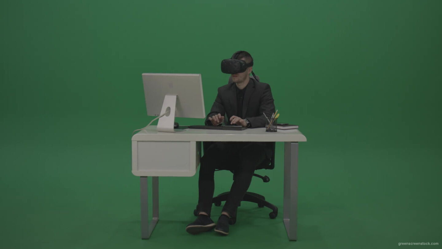 vj video background Young_Handsome_Businessman_Wearing_Dark_Suite_Sitting_At_The_Office_Table_Typing_Message_Using_VR_Glasse_Green_Screen_Wall-1920_003